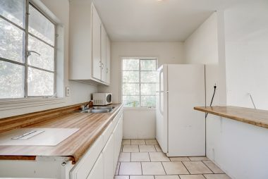 Guest unit kitchen with tile floor and refrigerator.