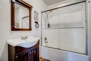 Hallway bathroom with shower in tub.