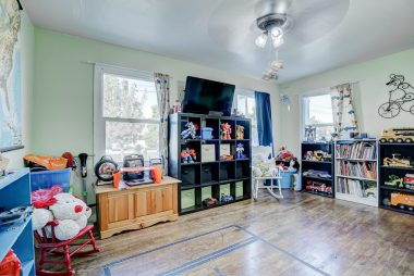 Front bedroom with ceiling fan and double pane windows.
