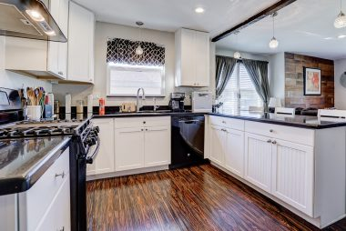 Remodeled kitchen with Silestone counter tops, dishwasher, 6-burner gas stove with optional griddle, and pendant lighting over the breakfast bar.