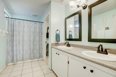 Master bathroom with double vanities and shower in tub, as well as tile flooring.