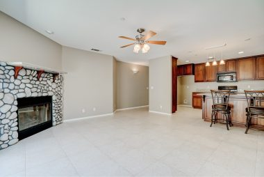 Family room fireplace with ceiling fan and tile flooring with view into open kitchen with pendant lighting, recessed lighting, and breakfast bar.