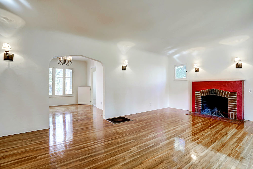 View of gorgeous living room with coved ceiling, fireplace, sconce lighting, and recently refinished original hardwood floors. View into the formal dining room with Dutch door leading to the kitchen.