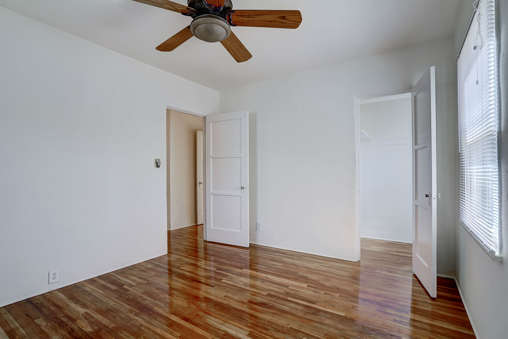 Back bedroom with ceiling fan and recently refinished original hardwood floors.