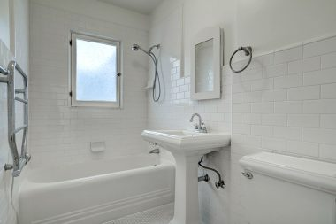Lovely bathroom with subway tile in shower and on walls, with honeycomb tile on floor, and pedestal sink.