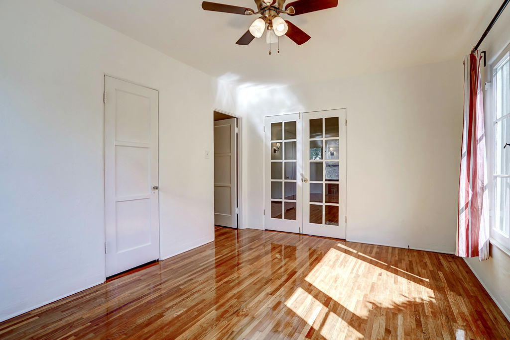 Alternate view of front bedroom with French doors leading to the living room. Open door to the left leads to the hallway and bathroom.