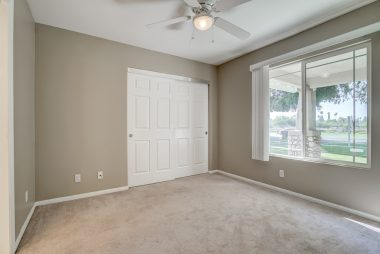 Front bedroom with newer carpeting, ceiling fan, and view of front yard through double pane windows.