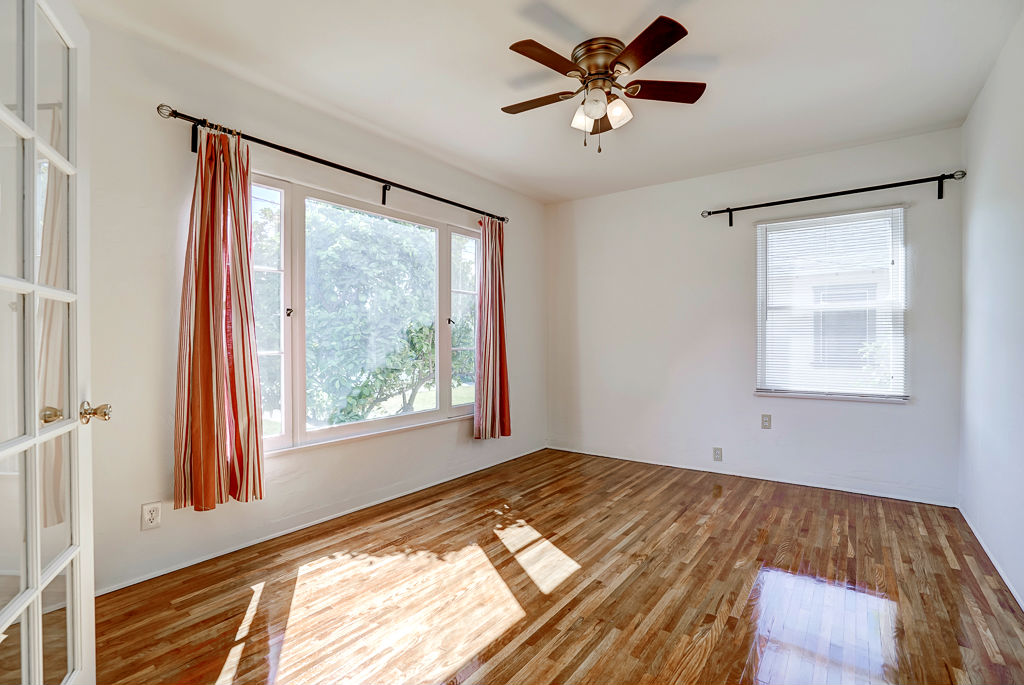 Front bedroom with French doors (simply add curtains for privacy), ceiling fan, and recently refinished original hardwood floors.