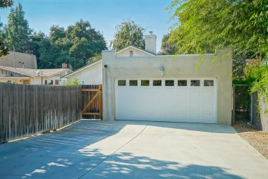 2-car detached garage with automatic roll up door, security lighting, and paved driveway.