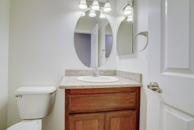 Hallway powder room with granite vanity.