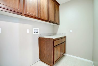Indoor laundry room with lots of cabinetry and granite counter top for folding and sorting.