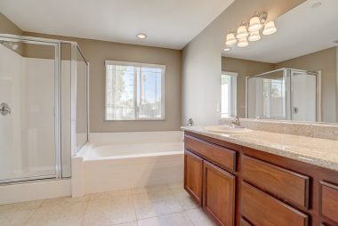 View of soaking tub and shower in master bathroom, including tile flooring.
