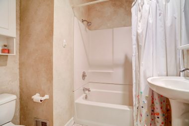 Hallway bathroom with shower in tub and pedestal sink.
