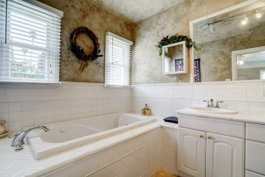 Remodeled master bathroom with spa tub, separate shower, and double sinks (only one pictured).