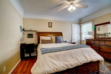 Another bedroom with ceiling fan and refinished hardwood floors, as well as a walk-in closet.