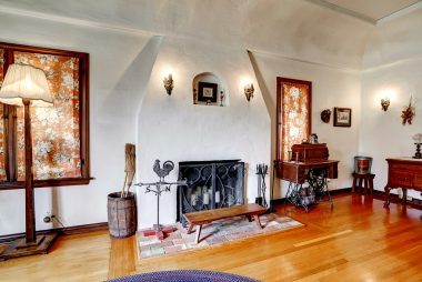Gorgeous gas and wood fireplace with sconce lighting and alcove.