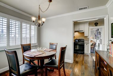 Formal dining room with crown molding, window shutters, and space for a sideboard.