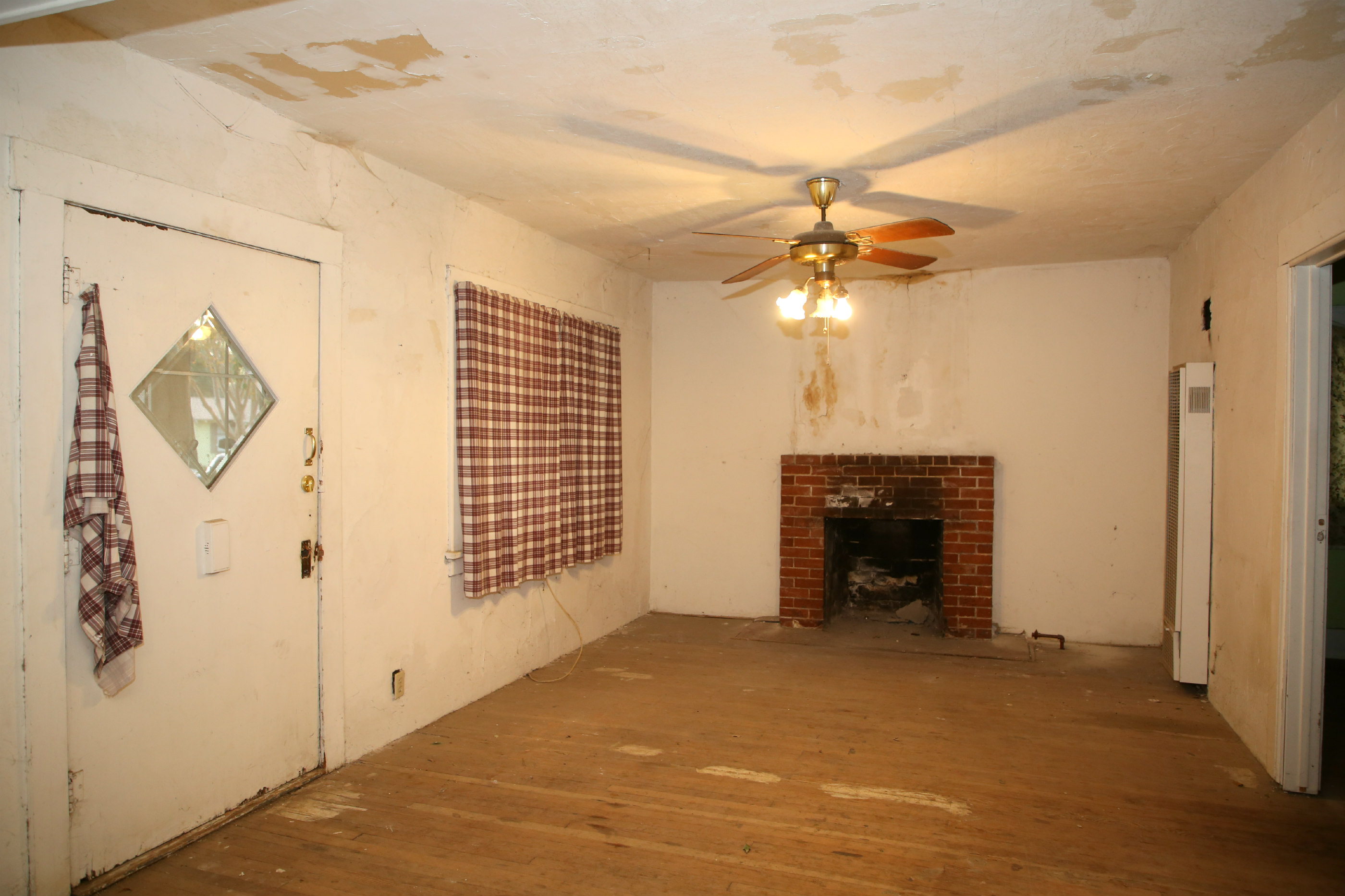 Living room with fireplace and wall heater.