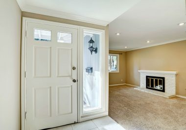 Front door entry with tile floor and step-down formal living room with fireplace and recessed lighting.