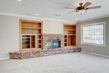 Family room media and book shelves with gas and wood-burning fireplace, recessed lighting, and ceiling fan.