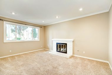 Step-down formal living room with gas and wood-burning fireplace and recessed lighting.