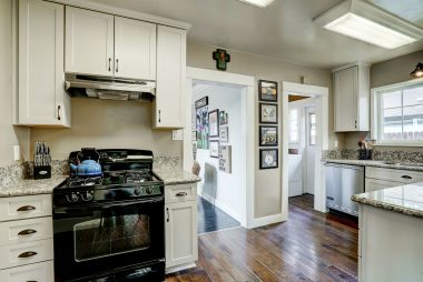 Black gas stove and black refrigerator are included. Entry to laundry room to the right.