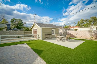 Different angle of backyard with artificial grass.