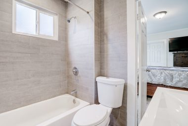 Remodeled bathroom with shower in tub.