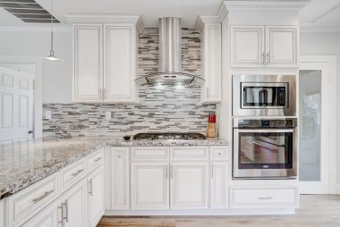 Stone counter tops, with glass tile back splash, gas range and stove, and built-in microwave.