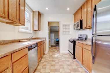 Lots of kitchen cabinetry, including dishwasher, gas stove, and built-in microwave.