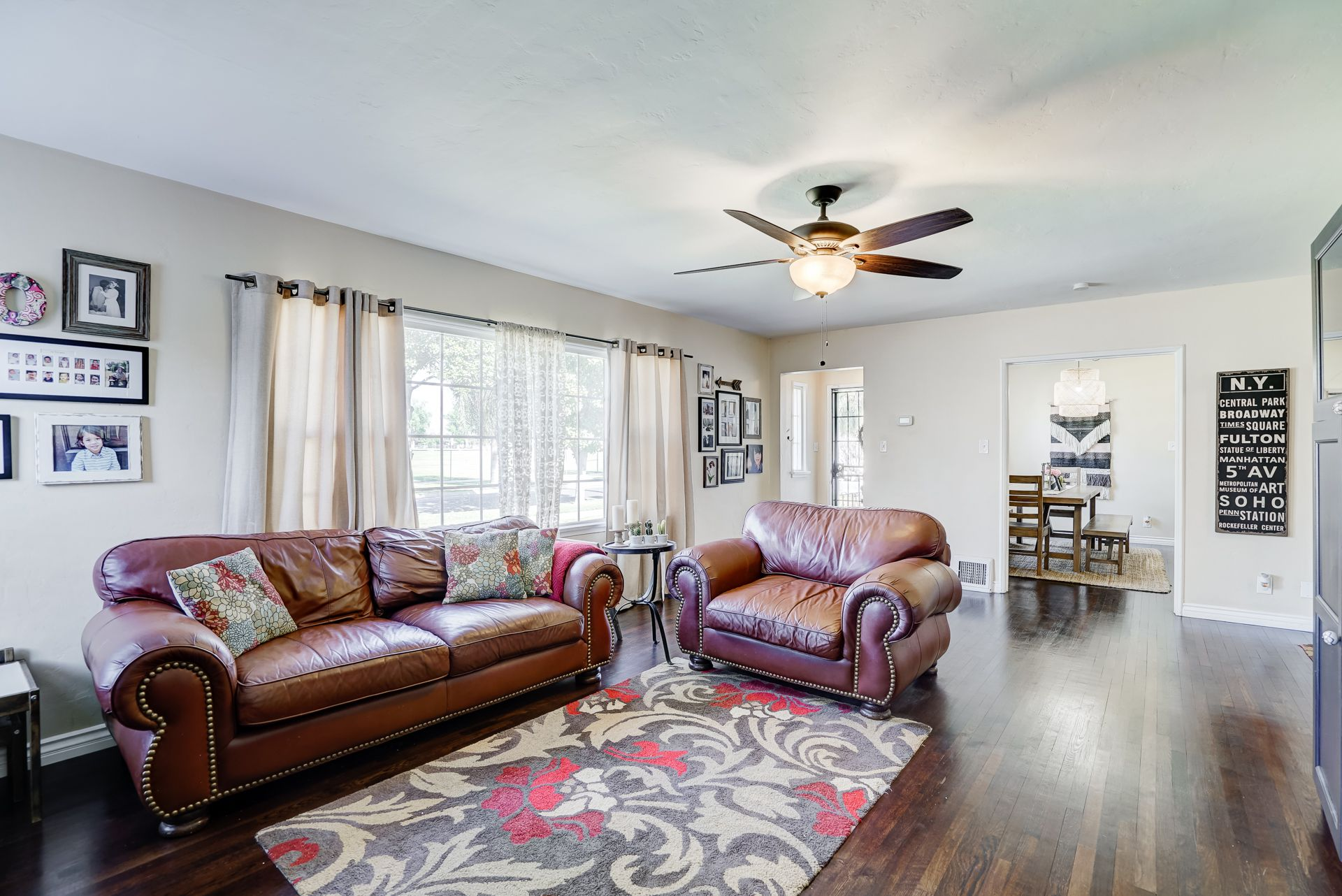 Spacious living room with included entertainment center, as well as ceiling fan and wood-burning fireplace.
