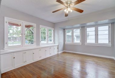 Large formal dining room with built-in cabinetry, original window frames and original hardwood floors.