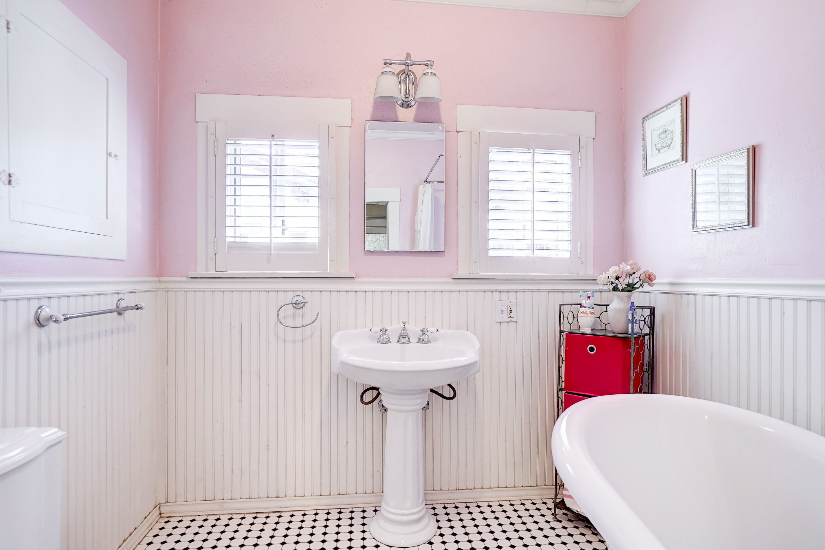 Remodeled hallway bathroom with tile floor and claw foot tub.