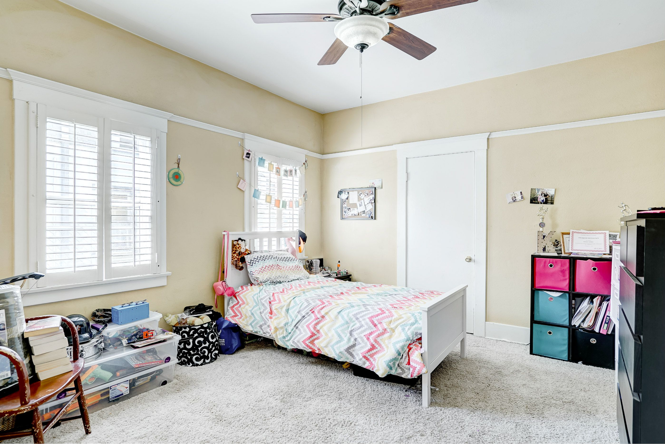 2nd of 4 bedrooms, this one with carpeting, window shutters, and ceiling fan.