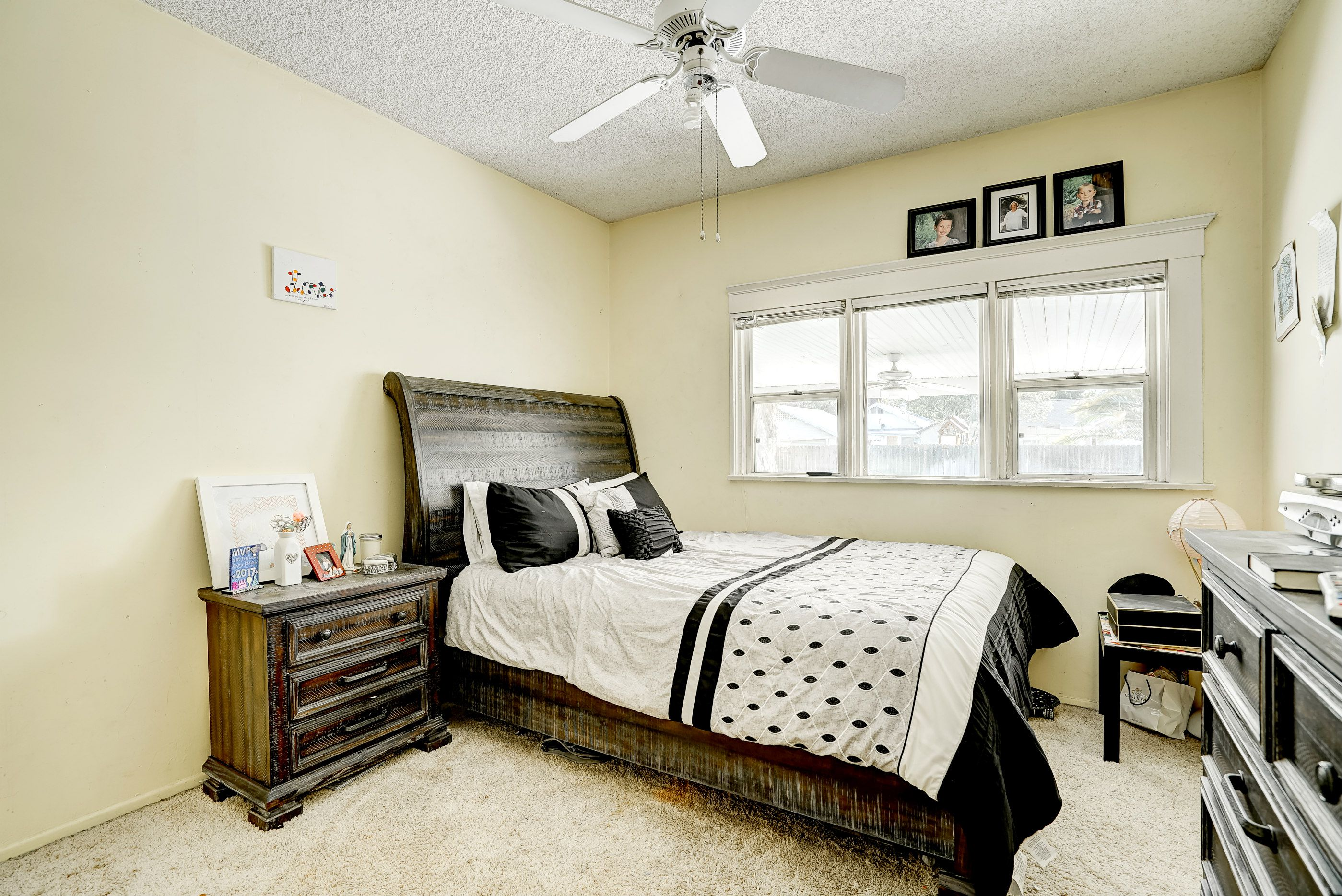 3rd of 4 bedrooms, this one with carpeting and ceiling fan, overlooking the back yard.