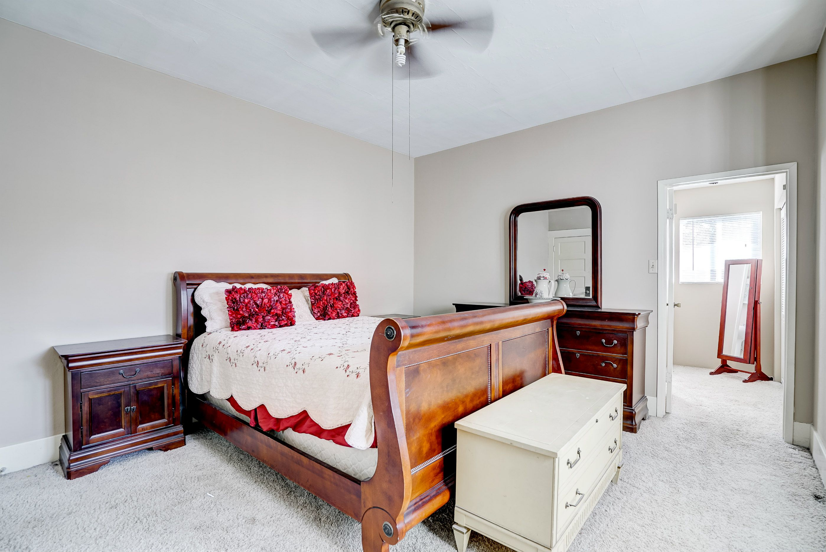 Master bedroom suite with ceiling fan, carpeting, and private master bathroom.