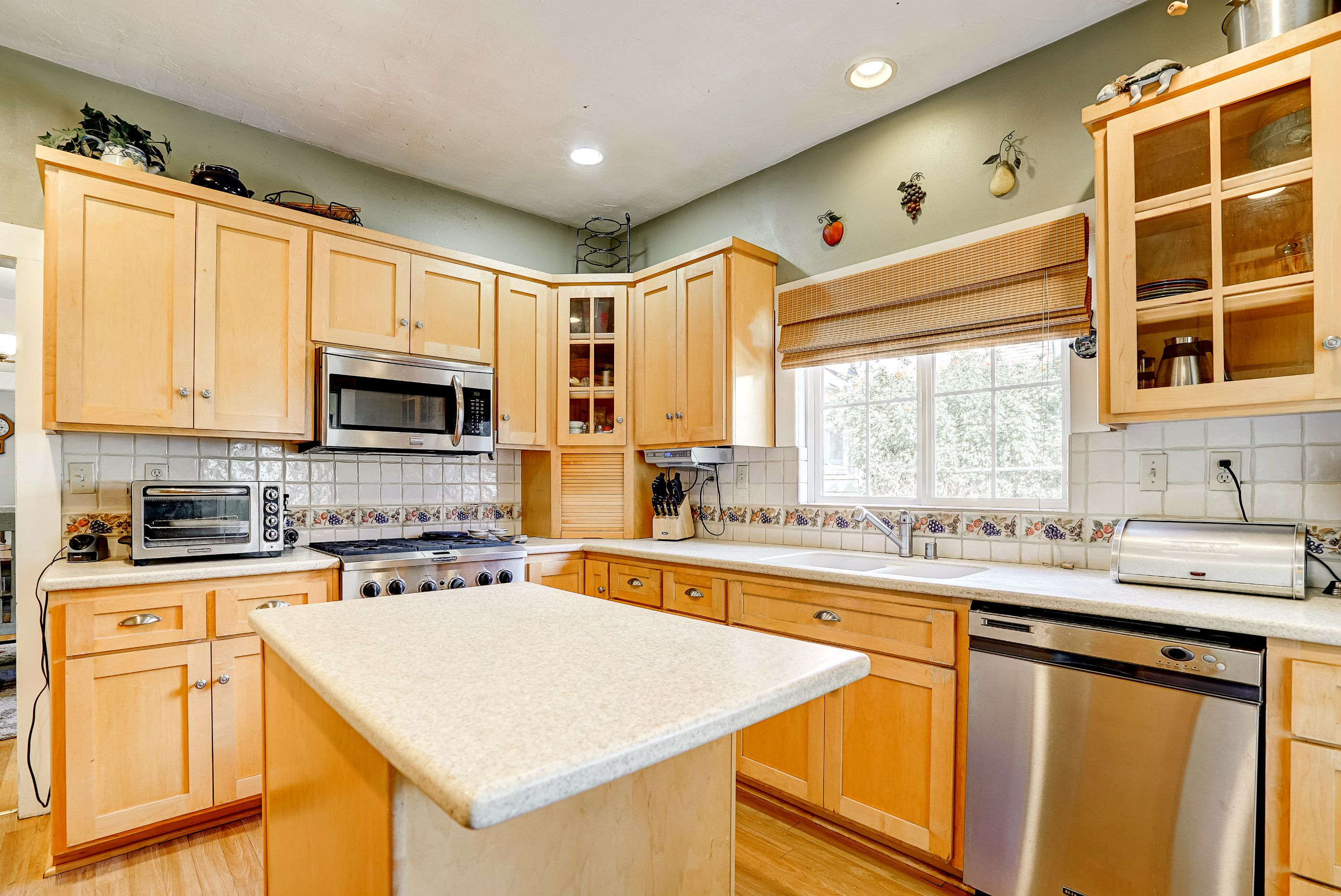 Wood floors, dishwasher, gas stove, and built-in microwave.