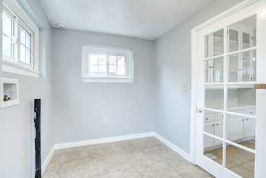 Separate indoor laundry room with cabinetry on other side of room.
