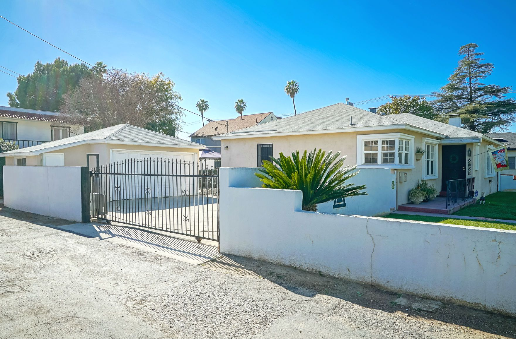 2-car detached garage with extra storage room, behind automatic driveway gate.