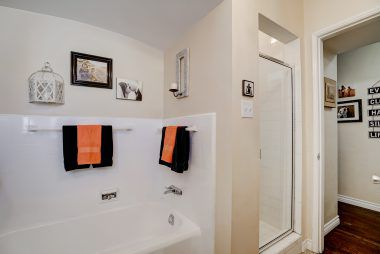 Hallway bathroom with separate shower and soaking tub.
