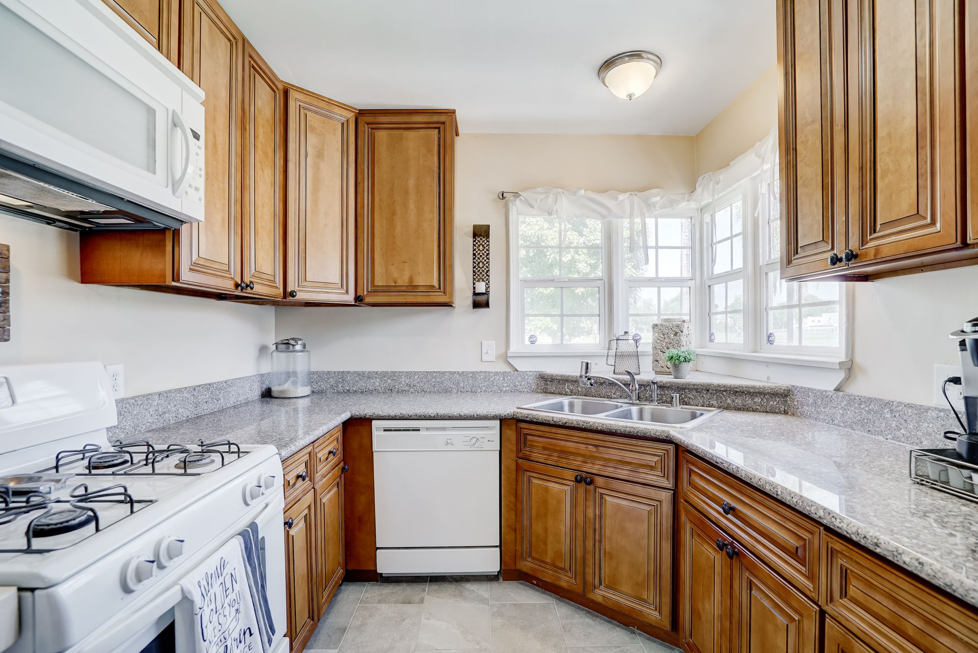 Updated kitchen with granite counter tops, new flooring, dishwasher, gas stove, built-in microwave, and corner sink with double pane windows.