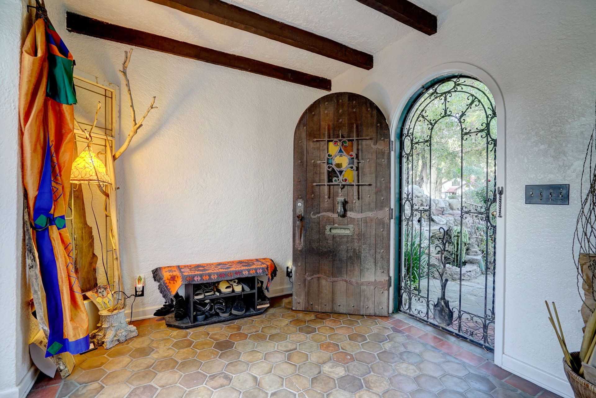 Entry with original ceiling beams and hand-crafted door.