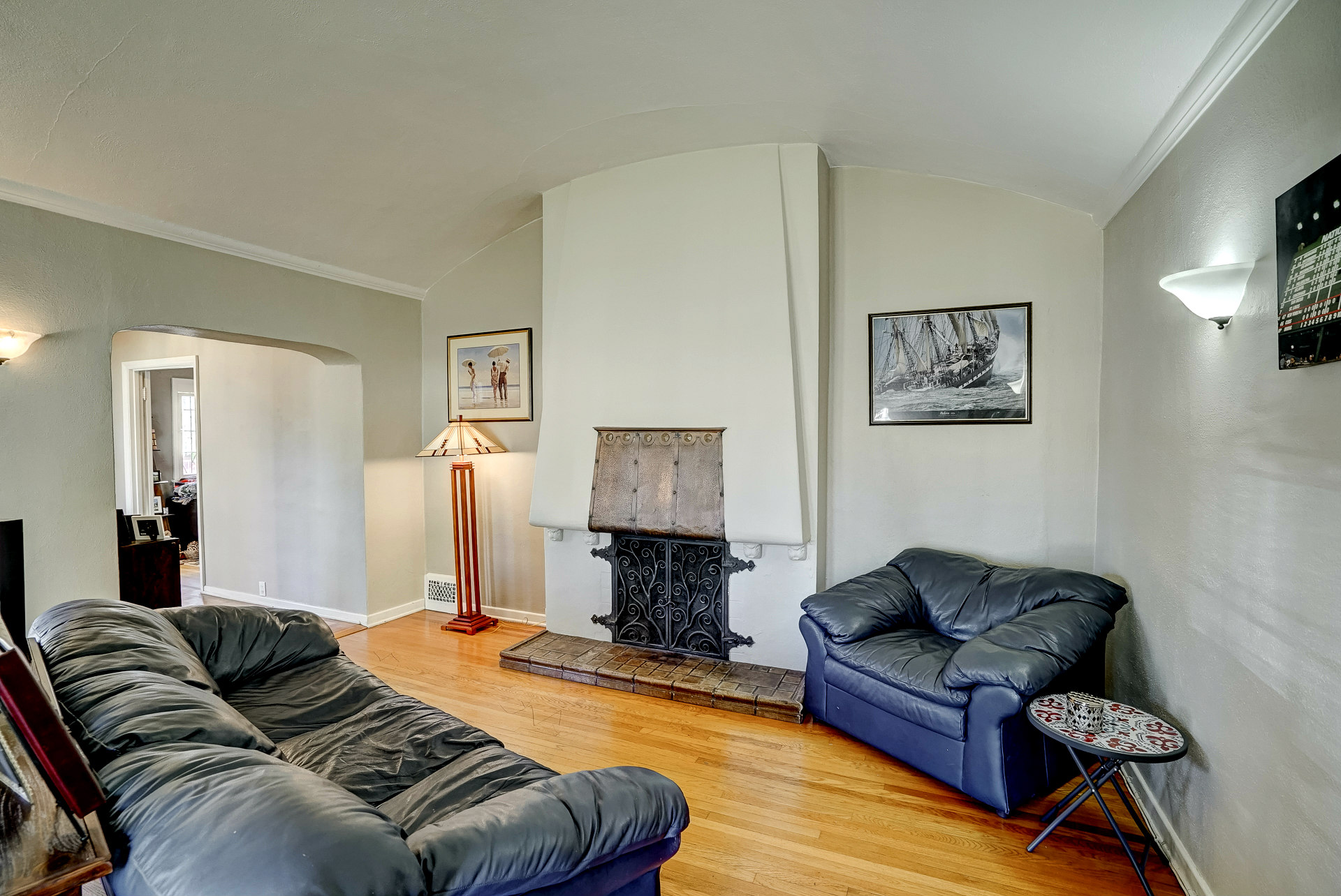 Round ceiling in living room with original hardwood floors and wood-burning fireplace.