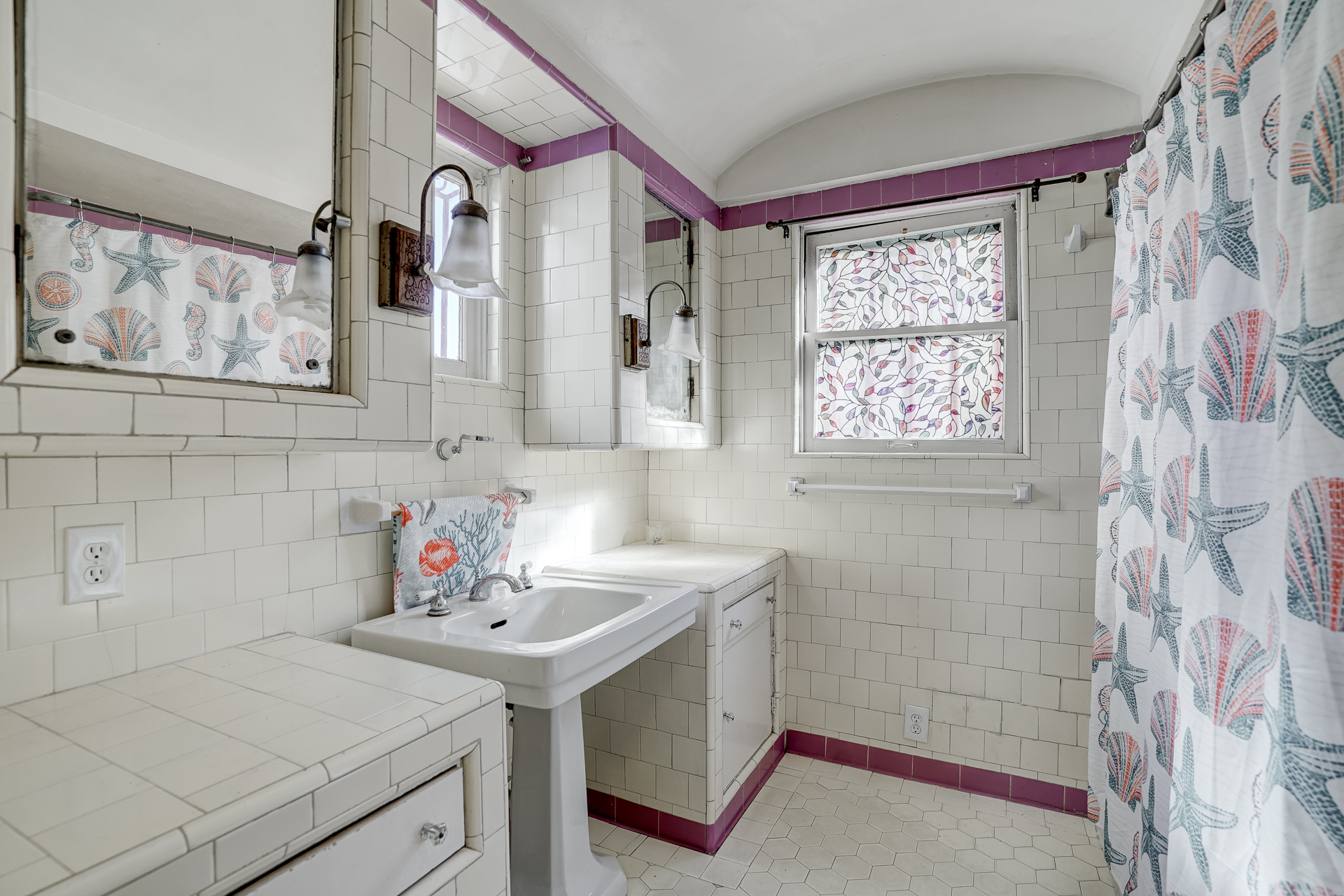 Vintage hallway bathroom with pedestal sink and shower in tub.