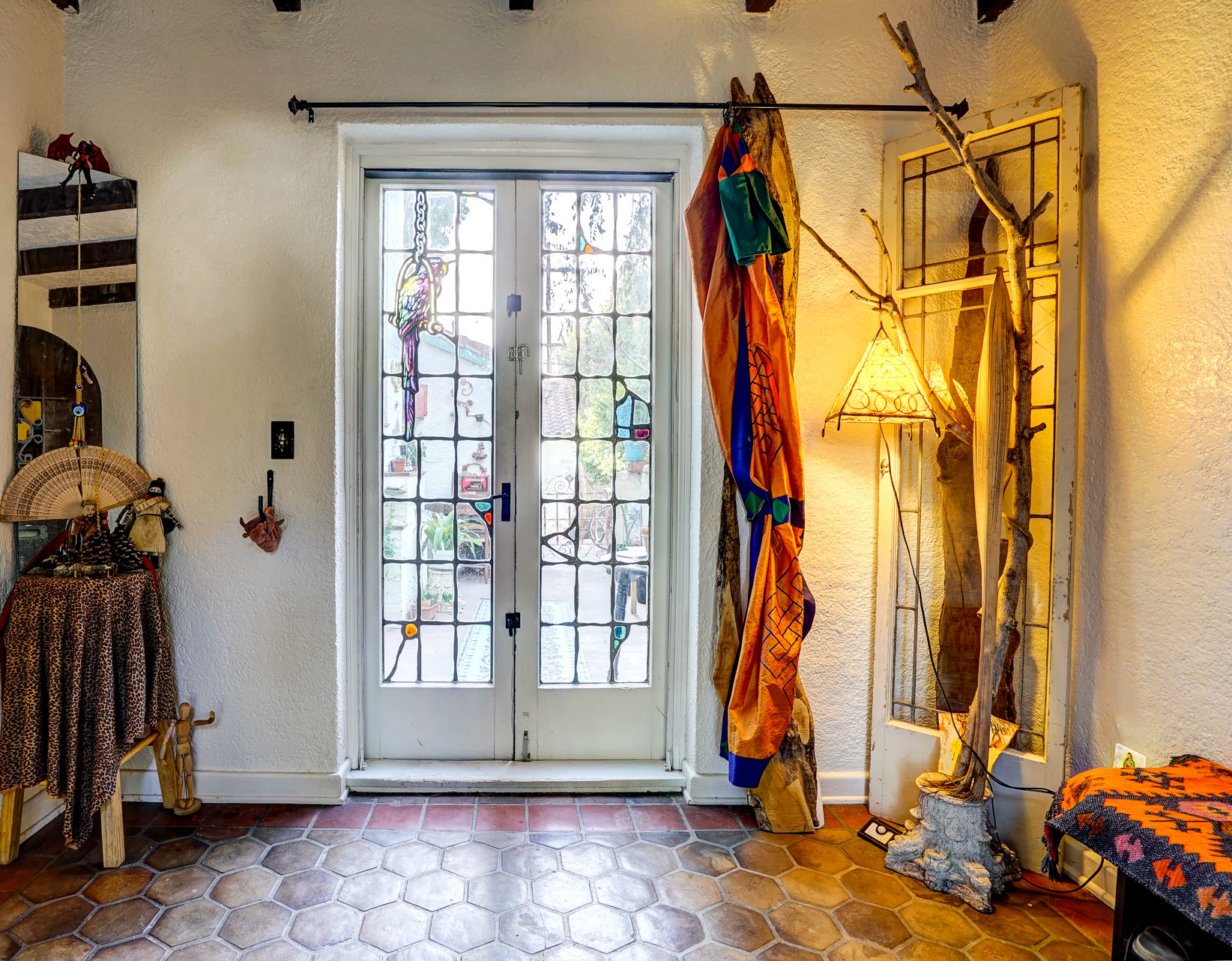 Alternate view of entry with original and amazing French doors with Jekel stained glass (note the parrot), overlooking the back patio.