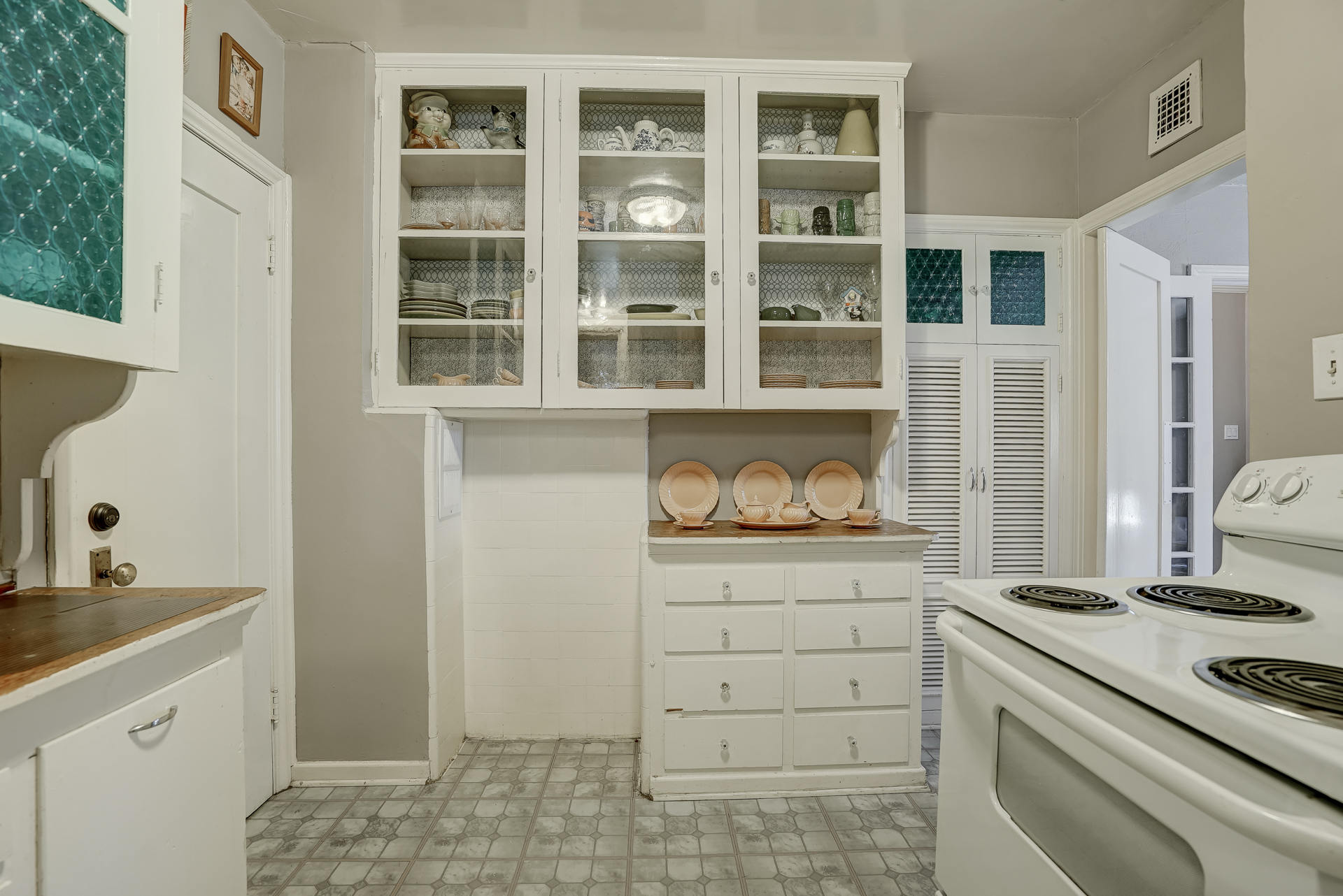 Alternate view of vintage kitchen with plenty of cabinetry. Doorway to left connects both units.