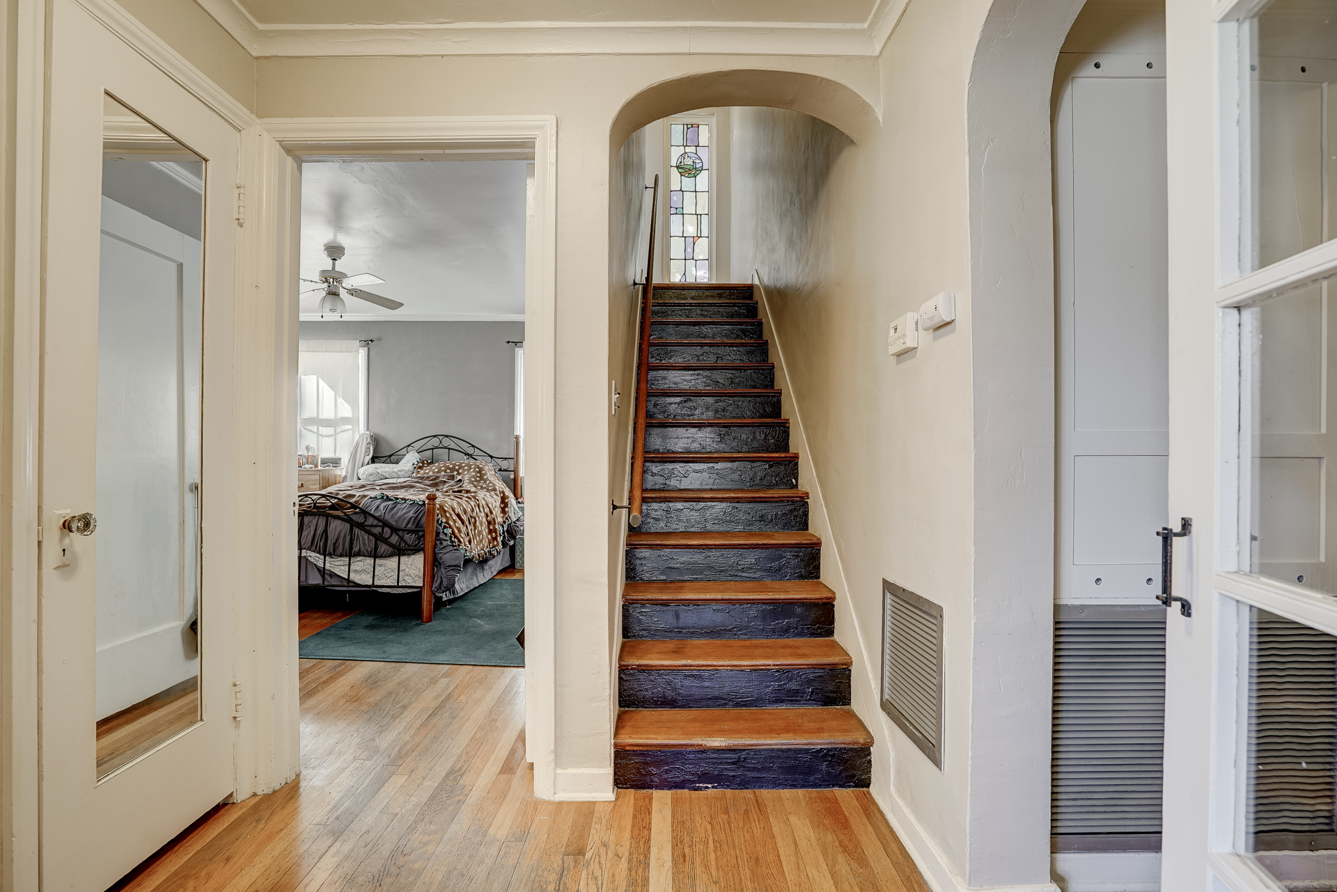 Stairway leading to upstairs bedroom,, sleeping porch, and half bath.
