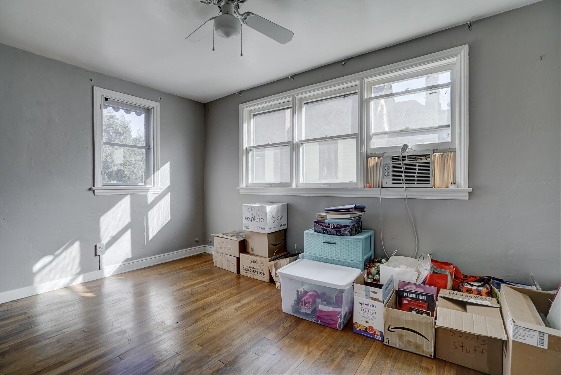 Upstairs bedroom with private half bath and original hardwood floors.