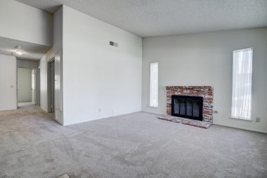 Living room fireplace, cathedral ceiling (a single story that feels very spacious) with view into hallway leading towards bedrooms.