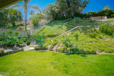 Partial view of gorgeously landscaped backyard with elaborate stairway to top of hill for amazing views.